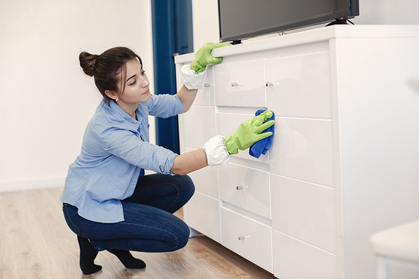 Woman with sponge and rubber gloves cleaning house